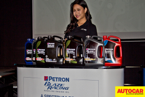 Model posing with line of petrol engine oil range at the Petron Malaysia HTP Engine Oil launch