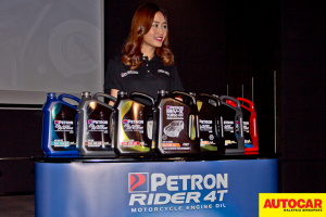 Model posing with line of diesel engine oil range at the Petron Malaysia HTP Engine Oil launch